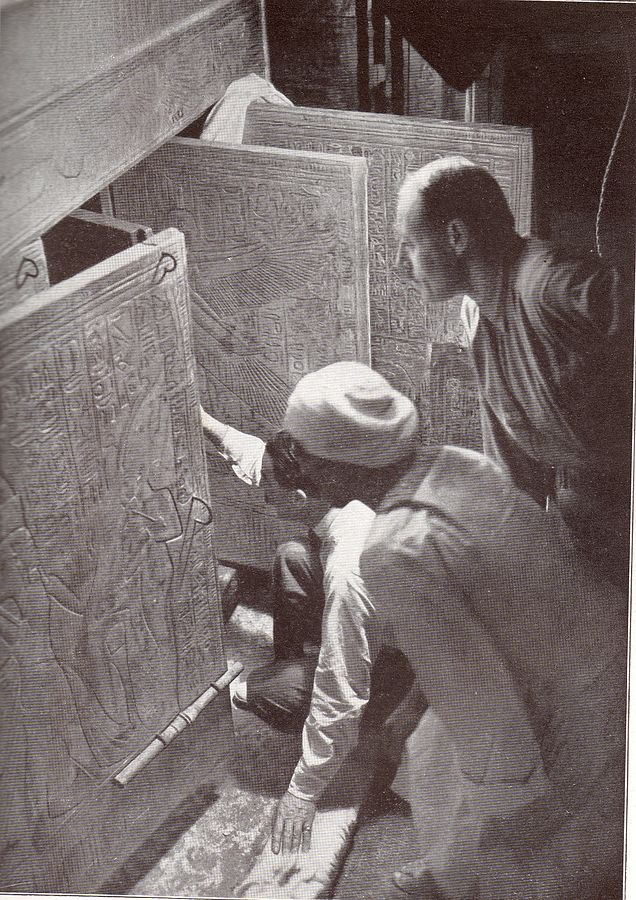 Howard Carter (kneeling), an Egyptian workman, and Arthur Callender at doors of burial shrines in Pharao Tutankhamen's tomb - public domain - The New York Times photo archive.